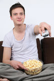 Young man sitting on a sofa and watching tv Royalty Free Stock Photography