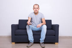 Young man sitting on sofa and watching tv at home Royalty Free Stock Photo