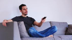 Man sitting on sofa and watching TV using remote control stock video