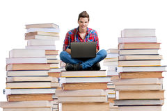 Young man sitting on a stack of books with a laptop royalty free stock photos