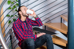Young  man sitting on stairs and drinking coffee Stock Image