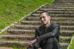 Young man sitting on the stairs with a happy face Stock Photo