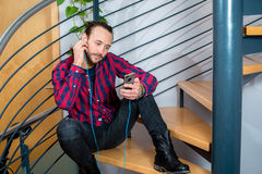 Young man sitting on stairs and listening music Royalty Free Stock Image