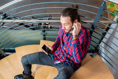 Young man sitting on stairs and listening music Stock Photos