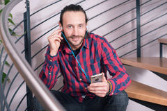 Young man sitting on stairs and listening music Stock Photography