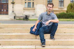 Young man sitting on stairs Stock Images