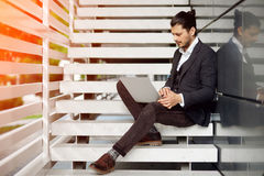 Young man sitting on the stairs using laptop Royalty Free Stock Photography