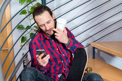 Young man sitting on stairs and using phone Royalty Free Stock Photography