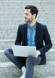 Young man sitting on steps with laptop Stock Image