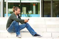 Young man sitting on steps listening to music with cell phone Royalty Free Stock Photo