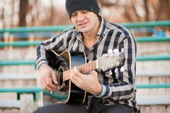 Young man sitting on steps playing guitar and singing royalty free stock photography