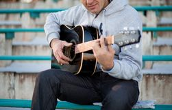 Young man sitting on steps playing guitar and singing royalty free stock photos