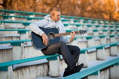 Young man sitting on steps playing guitar and singing royalty free stock image