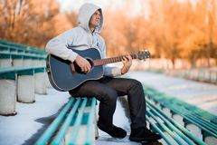 Young man sitting on steps playing guitar and singing stock photo