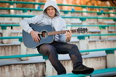 Young man sitting on steps playing guitar and singing stock image