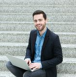 Young man sitting on steps and smiling with laptop Stock Image