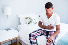 Young man sitting with stomach pain on bed. In bedroom Royalty Free Stock Image