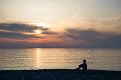 Young man sitting on the stone beach at sea sunset background Stock Image