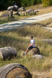 Young man sitting in the stone garden. Teenager resting on the rocks nursery at Costesti , Valcea , Romania Stock Photo