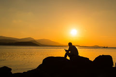 Young man sitting on the stone play smartphone Royalty Free Stock Photography