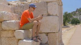 Young man sitting in ancient Agora in archaeological site of Patara. Young man sitting on the stones and looking at phone in the ancient Agora in archaeological stock video footage