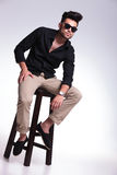 Young man sitting on a stool Stock Photo