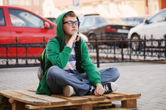 Young fashion man sitting on city street Stock Photography