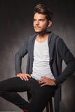 Young man sitting in studio with hands on waist looking away Stock Photo