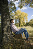 Young man sitting on suitcase Stock Photo