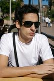 Young man sitting with sun glasses Royalty Free Stock Photo