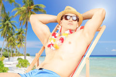 Young man sitting on a sun lounger on a beach next to a sea Stock Photography