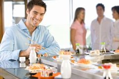 Young man sitting at sushi bar, smiling, portrait Royalty Free Stock Photo