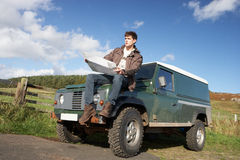 Young man sitting on SUV Royalty Free Stock Images