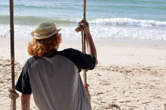 Young man sitting on the swing on the beach, feeling so sad ,alone,lonely Royalty Free Stock Photography