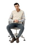 Young man sitting in swivel chair Royalty Free Stock Photos