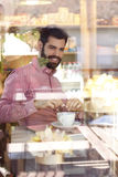 Young man sitting at table in coffee shop. Stock Photo