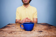 Young man sitting at table with cup of coffee Royalty Free Stock Photos