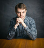 Young man sitting at a table. Stock Photography
