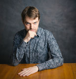 Young man sitting at a table. Royalty Free Stock Image