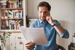 Man reading paperwork and talking on a cellphone at home. Young man sitting at a table in his living room reading paperwork and talking on a cellphone while Stock Photo
