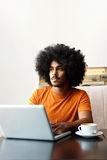 Young man sitting at table with laptop Royalty Free Stock Photography