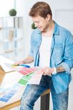 Young man sitting on the table and looking at color palettes stock photography