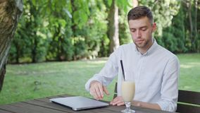A Young Man Drinking Milkshake in the Park. A young man sitting at the table in the park and drinking a milkshake. Medium shot. Soft Focus stock photo