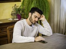 Young man waiting for call. Young man sitting at table and waiting for call or message at home Stock Image