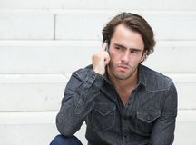 Young man sitting and talking on mobile phone Stock Image