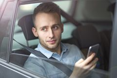 Young man sitting in a taxi Stock Image