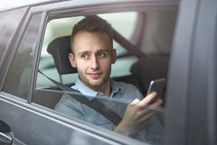 Young man sitting in a taxi Stock Photos