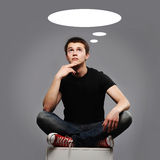 Young man sitting and thinking about something Royalty Free Stock Photos