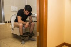 Young Man Sitting on Toilet. Young Dark Haired Man Sitting on Toilet with Pants Around Ankles Stock Photography