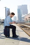 Young man sitting at train station platform text messaging stock image